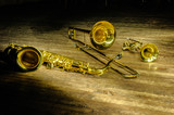 Brass and wind instruments - saxophone, trombone, trumpet on stage with backlight.