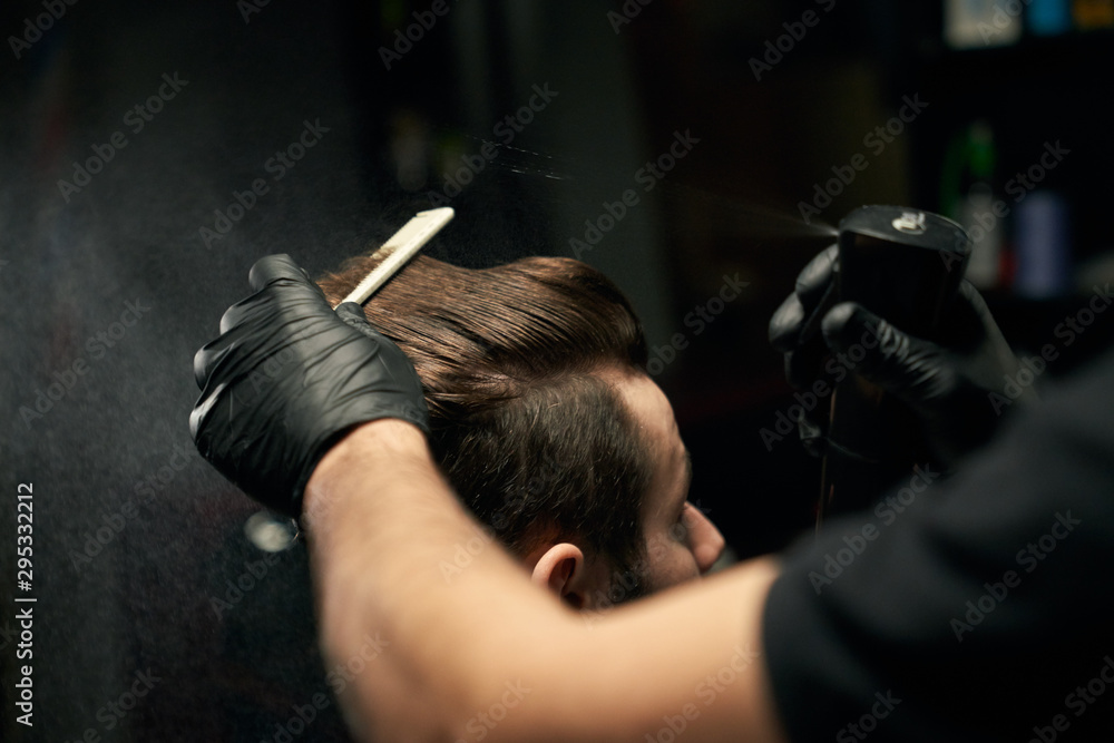 Fototapeta Crop of barber hands making new haircut for male client