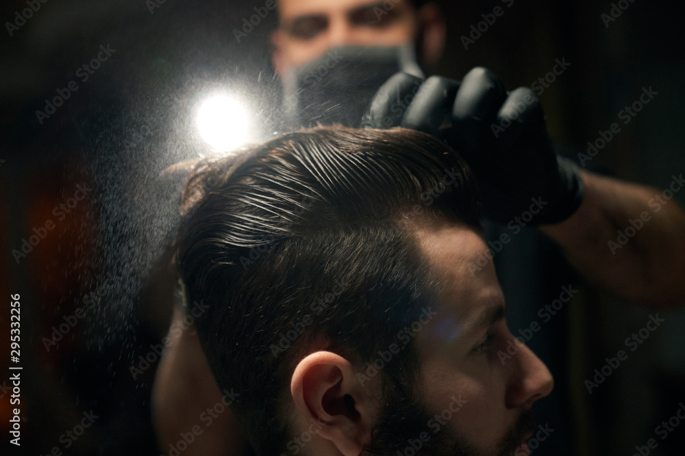 Fototapeta Close up of man's hair combing by barber in black gloves