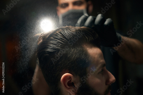 Close up of man's hair combing by barber in black gloves