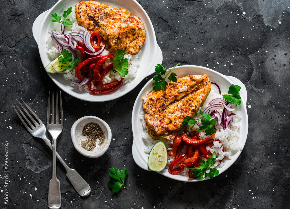 Fototapety, obrazy: Baked spicy chicken breast with sweet pepper and rice -  delicious mexican style lunch on a dark background, top view. Fajitas bowl