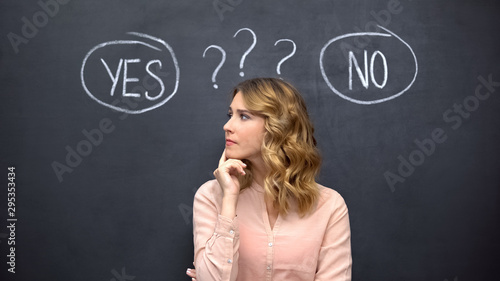 Puzzled woman choosing between yes no, stereotype of uncertain female thinking Fototapet