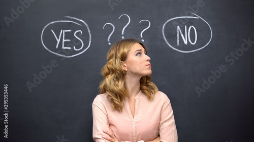 Fotomural  Uncertain female choosing between yes no, standing against blackboard, dilemma