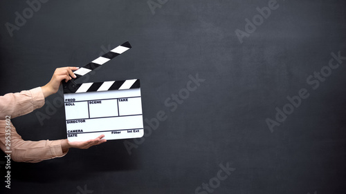 Fotografia Female hands using clapperboard against black background, shooting movies