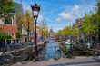canvas print picture - Bicycles in Amsterdam street near canal with old houses