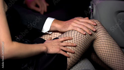 Man touching lady leg in fishnet stockings, strong temptation, harassment risk - 295357267