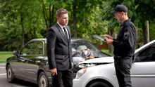 Male Police Officer Filling Car Crash Report, Businessman Standing Broken Auto