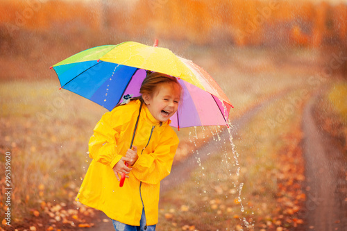 obraz lub plakat Happy girl with rainbow umbrella in autumn park