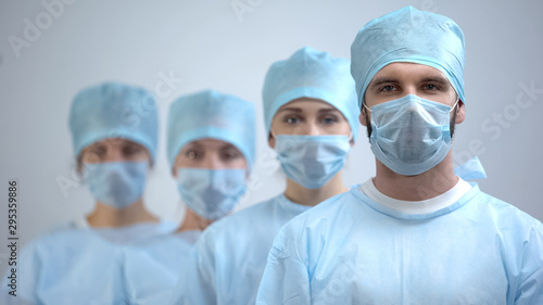 Professional surgeon team in mask and uniform looking at camera, hospital work - 295359886