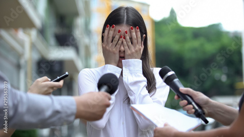 Cuadros en Lienzo Ashamed businesswoman closing face with hands on press conference, scandal