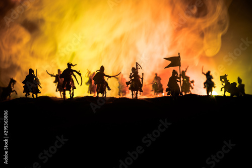 Foto op Canvas Paarden Medieval battle scene with cavalry and infantry. Silhouettes of figures as separate objects, fight between warriors on dark toned foggy background. Night scene.