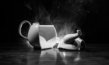 Broken Teapot On A Dark Toned Foggy Background. Pieces Of Ceramic Teapot On Wooden Table.