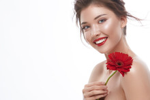 Pretty Woman With Perfect Smile Holding Red Flower And Looking To The Camera