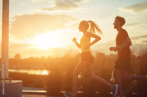 Foto  Modern woman and man jogging / exercising in urban surroundings near the river