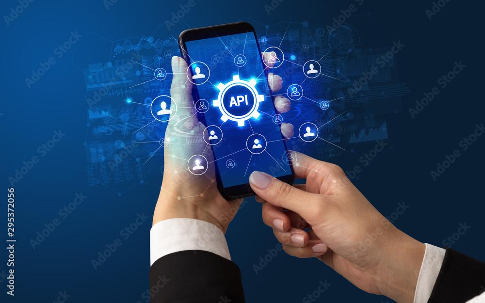 Fototapeta Female hand holding smartphone with API abbreviation, modern technology concept