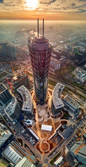 Panel Szklany PodświetlaneBeautiful panoramic aerial drone view to the center of Warsaw City and The Warsaw Spire - 220 metre neomodern office building on European square (Plac Europejski)