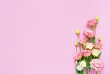Pink and white eustoma flowers bouquet on pink background. Copy space, top view. Holiday backgrou