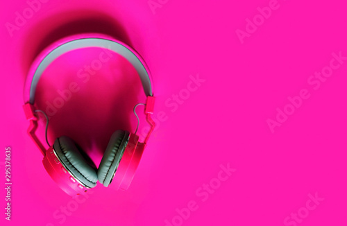 Pink headphone isolated on pink background . - 295378635