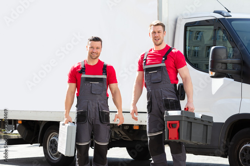 obraz lub plakat Portrait Of A Smiling Young Male Technicians Holding Tool Box