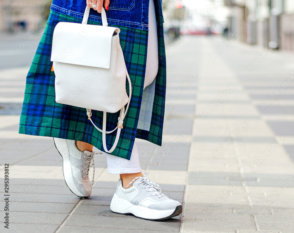 Fototapety, obrazy: Fashionable bag close-up in female hands.Girl walks in the city outdoors. Stylish modern and feminine image, style. A woman in a raincoat, coat and with a white backpack. girl in sneakers and jeans.