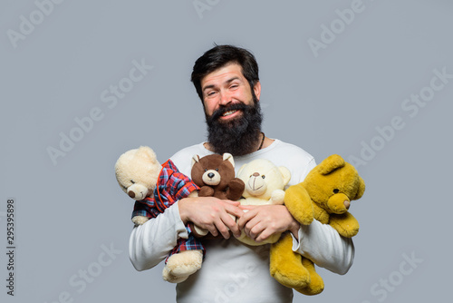 Teddy bear present. Bearded man with