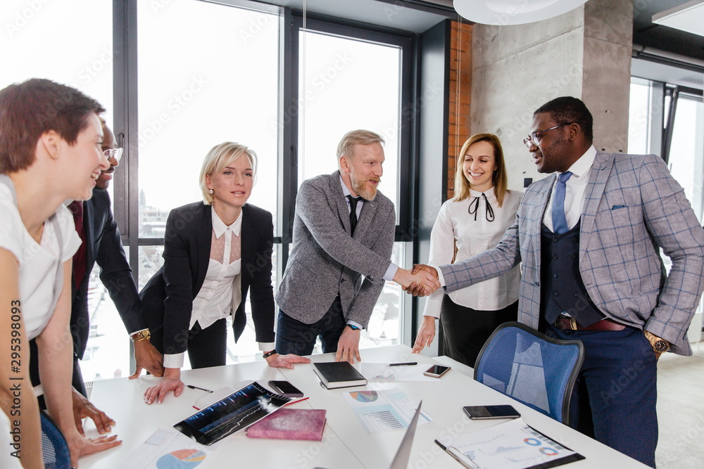 Fototapeta Businessmen of different ages shake hands with African partners standing at the table in the office