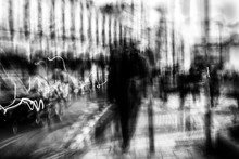 Long Exposure Of Pedestrians Walking Along The High Street - Intentional Camera Shake To Introduce An Impressionistic Effect And Light Trails - Creative Filter Applied Creating A Ghostly Aesthetic