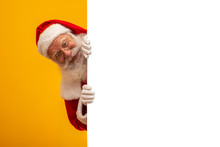 Happy Santa Claus Looking Out From Behind The Blank Sign Isolated On Yellow Background With Copy Space