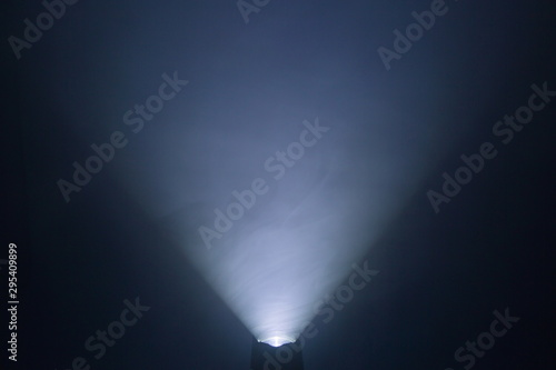 Photo flashlight and light beam in dark mist room at night