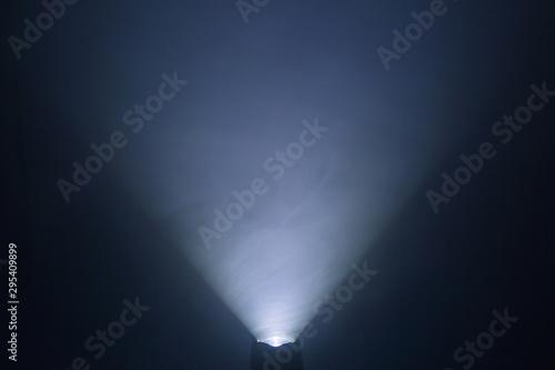 Canvas Print flashlight and light beam in dark mist room at night