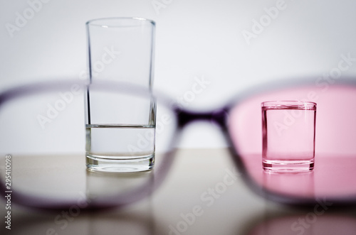 Optimism, illustrated by comparing less than half full glass in one frame of glasses with full smaller glass through rose tinted lens in another frame Canvas Print