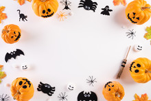 Top View Of Halloween Crafts, Orange Pumpkin, Ghost, Bat And Spider On White Background With Copy Space For Text. Halloween Concept.