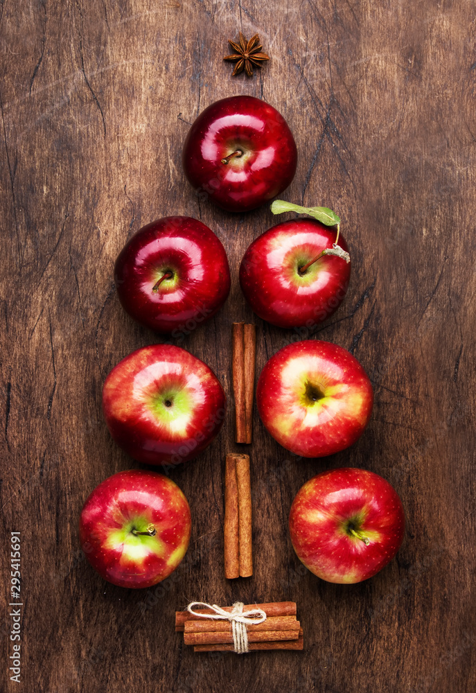Fototapeta Creative Christmas tree made from red apples, cinnamon and anise star on wooden brown background