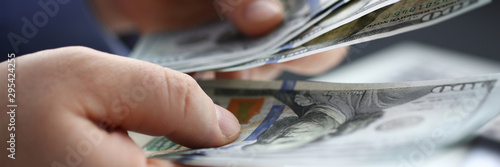 Fotomural Businessman considers cash dollars in office issues salaries to employees with black cash divides profits as result of illegal transactions everyone is happy