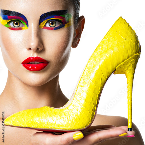 Fotografie, Tablou beautiful woman with vivid make-up of eyes holds the yellow high heel
