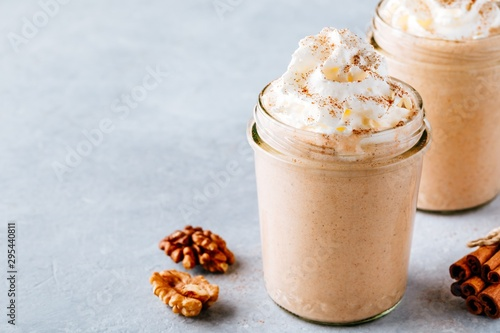 Fototapeta Pumpkin and carrot spice latte with whipped cream and cinnamon in glass jars