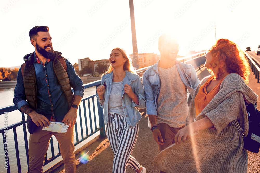 Fototapety, obrazy: Group of tourists enjoying on vacation, young friends having fun walking on city street during sunset.
