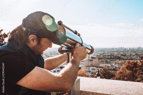 Fotografie, Tablou  A man looks into the observation tube from the observation deck from the height