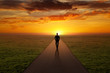 canvas print picture - Man walking alone on a road towards the sunset