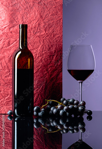 Fototapeta  Bottle and glass of red wine on a black table.