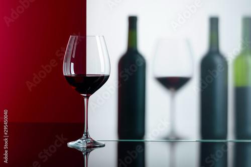 Obraz na plátně  Bottles and glasses of red wine on a black reflective background.