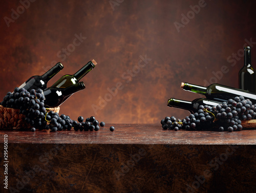 Fotografie, Obraz  Juicy blue grapes and bottles of red wine on a brown background.