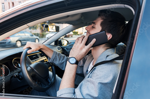 Fototapeta  Driver businessman is talking on smartphone behind steering wheel of car