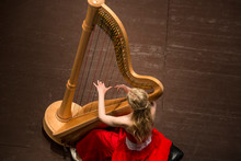 Beautiful Girl Playing A Harp In A Concert Hall During A Concert Of Classical Music