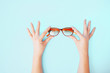 Leinwanddruck Bild - Female hands gently holding glasses on bleached coral background.