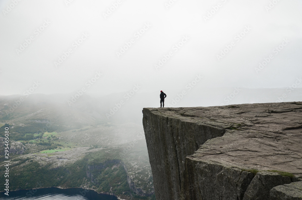 Fototapety, obrazy: A man standing on the edge of the cliff Preikestolen in Norway. Moody summer weather and beautiful scenery.