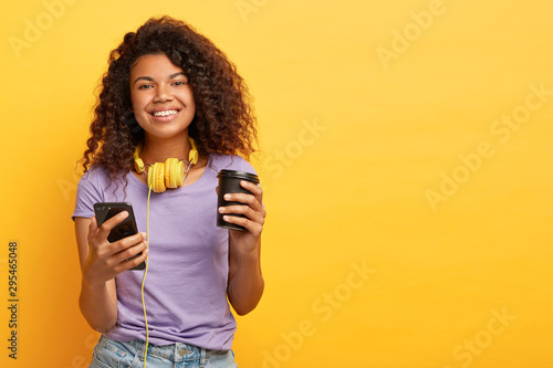 Smiling curly haired female watches video on mobile phone during coffee break, listens audio tracks via headphones, has happy mood, wears casual outfit, isolated over yellow background, blank space - 295465048
