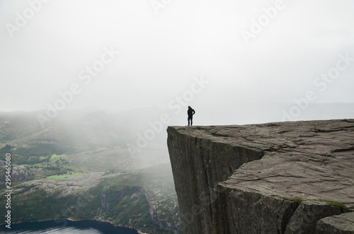 Foto op Plexiglas Wit A man standing on the edge of the cliff Preikestolen in Norway. Moody summer weather and beautiful scenery.