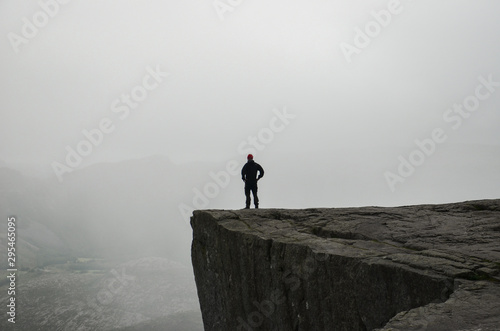 Fotografie, Obraz A man standing on the edge of the cliff Preikestolen in Norway