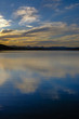 Vertical view of a sunset in a lake under a cloudy sky